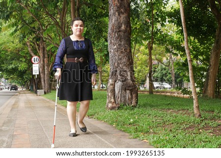 Asian blind person woman walking on sidewalk with a long white cane a mobility tool used to detect objects in the path, also helpful for onlookers in identifying the user as blind or vision disability Stock fotó ©