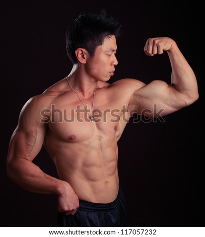 Asian Body Builder flexing left bicep showing off his abs