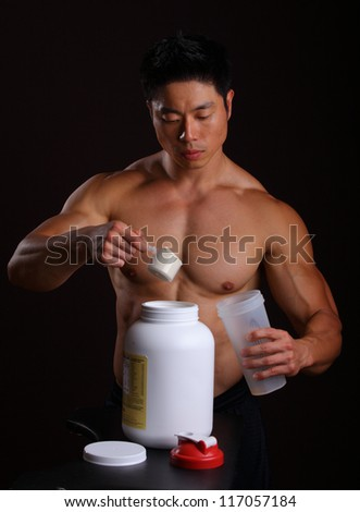 Asian Body Builder pouring a scoop of protein mix in to a mixing jar