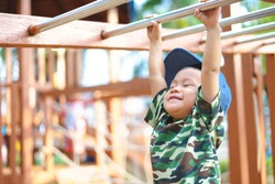 Asian boy about 1 year and 9 months in military suit playing at kid training playground for muscle development