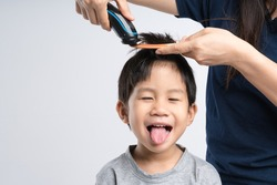 Asian boy about 4 year old got hair cut at home by his mother with electric cordless clippers