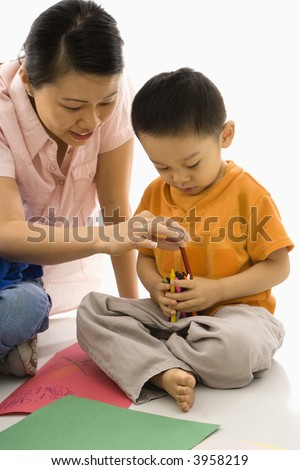 Asian boy and mother coloring with crayons.