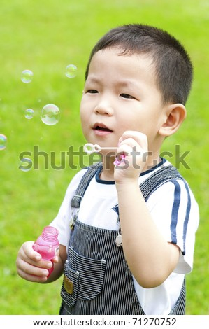 Asian boy blowing bubbles outdoor