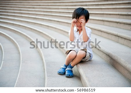 Asian boy crying on stairs