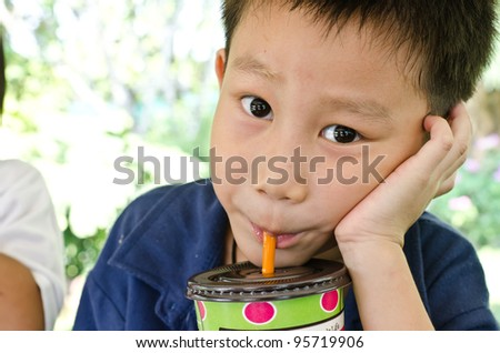 Asian boy drinking water and look at camera