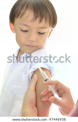 Asian boy during medical injection on white background.