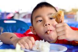 Asian boy Eating Chicken/child eating a chicken leg