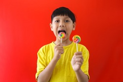 Asian boy eating lollipop  candy on red background