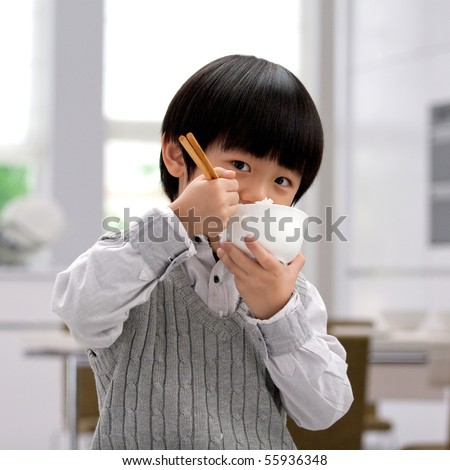 Asian boy eating rice with chopsticks - stock photo