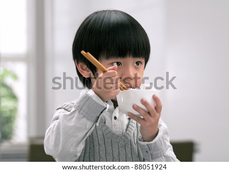 Asian boy eating rice with chopsticks