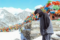 Asian boy hiking on the high snow mountain with blowing Tibetan prayer flags, feeling cold and hiding his hands in his pockets on a windy day.