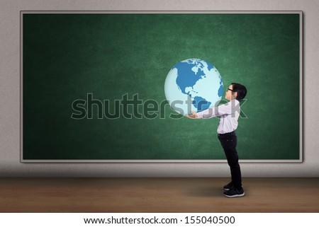 Asian boy holding a globe on the classroom