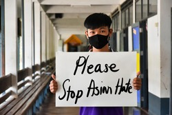 Asian boy holds a paper with English words 'Please Stop Asian Hate', concept for calling the international community to stop the hatred of the Asian people that have caused spreading of the covid-19.