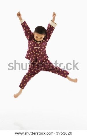 Asian boy in traditional attire jumping into air excitedly against white background.