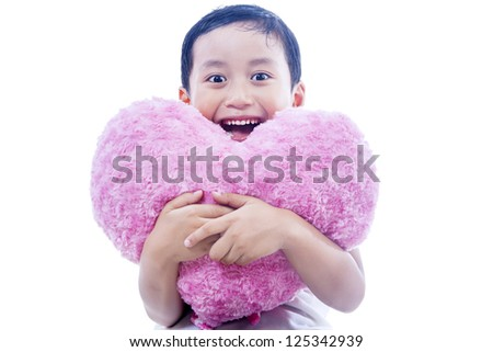 Asian boy is smiling cheerfully while holding a pink heart shape pillow on white background