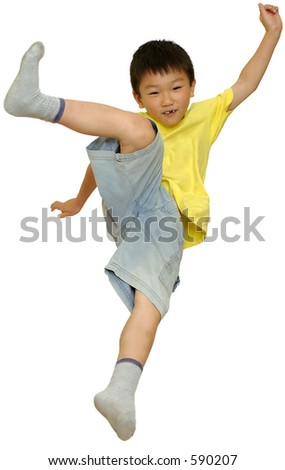 Asian boy jumping on bed doing high kick on white