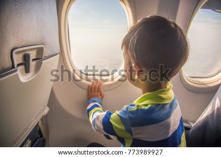 asian boy looking aerial view of sky and cloud outside airplane window while sitting on airplane seat. #773989927