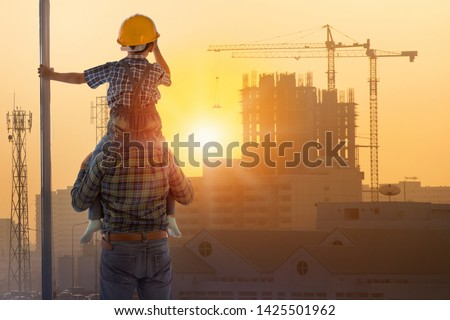 Asian boy on father's shoulders with background of new high buildings and silhouette construction cranes of evening sunset, father and son concept