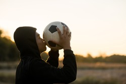 Asian boy player football soccer and kiss ball in the meadow with sunset background