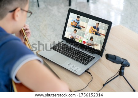 Asian boy playing acoustic guitar virtual happy hour meeting for play music online together with friend in video conference with laptop for a online meeting in video call for social distancing. Сток-фото ©