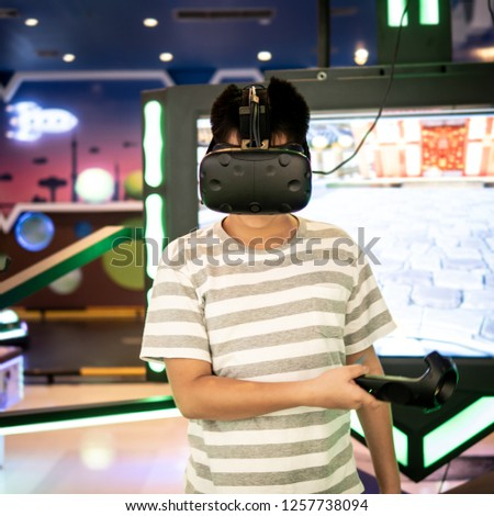 Asian boy playing video game in virtual reality headset and handheld controller developed