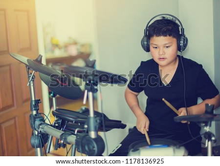 Asian boy put black tshirt and headphone learning and play electronic drum with wooden drumsticks in music room.