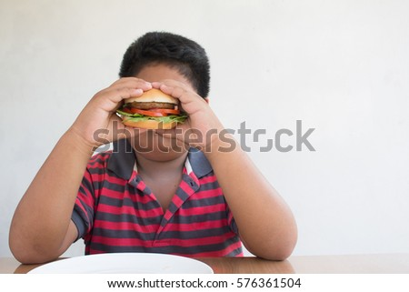 Asian boy's eating a hamburger, junk food unhealthy for children. #576361504