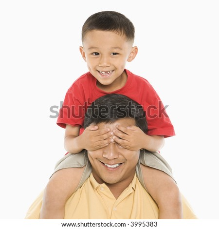 Asian boy sitting on father's shoulders with hands over his eyes in front of white background.