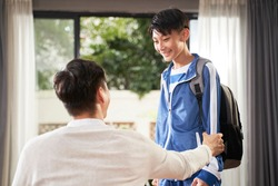 Asian boy talking to his father after school with paper in hand and backpack over shoulder