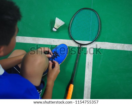 Asian boy tie his sport shoe inside badminton court.