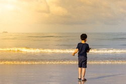 Asian boy walking on a beach in the morning