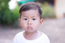 Asian boy wearing a white shirt, looking at the camera, not smiling.