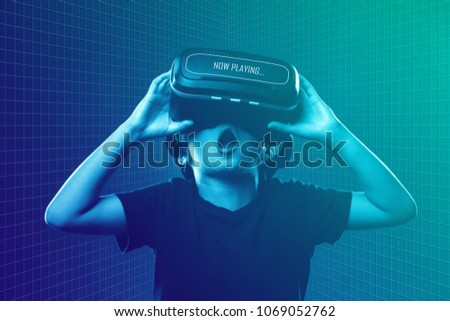 Asian boy wearing virtual reality (VR) googles streaming movies. Adoption of technology in entertainment.  Futuristic movie watching experience. Mixed media.