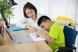 Asian boy with disability in wheelchair drawing picture with Laptop and mother at home. Supportive, Care, Coexistence and education.
