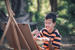 Asian boy with Down's syndrome is happily drawing a picture  in the garden.Drawing, Art Therapy