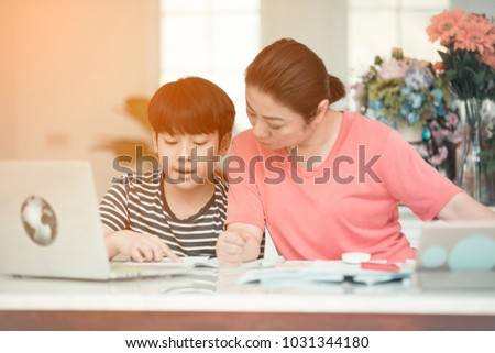 Asian boy with mother teaching and learning your homework at home  #1031344180