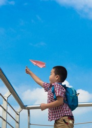 Asian Boy 5 years old, under the blue sky happily playing with paper plane,
