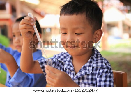 Asian boys are having fun doing science experiments. He experimented with different color combinations and noticed the changes.