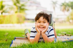 Asian boys are in the mood to relax on weekends in the park in the morning sunshine,concept of bright childhood, learning outside the classroom and finding lessons outside the classroom.