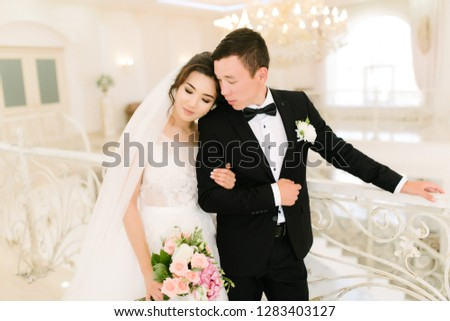 asian bride and groom posing on the stairs #1283403127