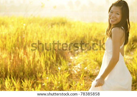 Asian bride at outdoor in a morning surrounding by golden sunlight