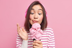 Asian brunette young woman looks at appetizing ice cream licks lips eats yummy frozen dessert listens music via headphones dressed in striped jumper isolated over pink background. Mmm how tasty