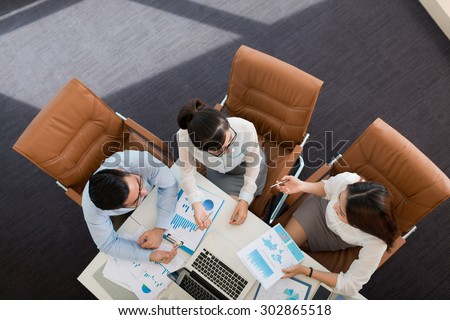 Asian business colleagues discussing financial reports, view from the top - Shutterstock ID 302865518