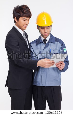 Asian business man and engineer have a pad PC isolated on white
