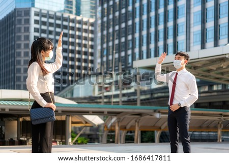 Asian business man and woman greet and say hello with business colleague and wearing mask standing distance of 1 meter distance protect from COVID-19 viruses for social distancing  for infection risk