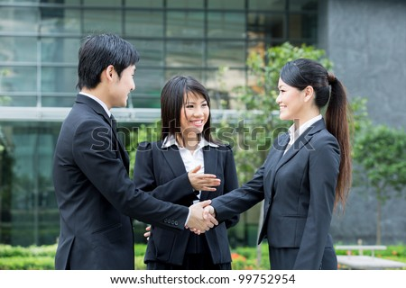 Asian business man and woman shaking hands. - stock photo