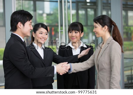 Asian business man and woman shaking hands.