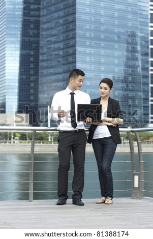 Asian Business man and woman using a Laptop outside