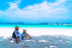 Asian business man in summer vacation trip, Traveler man relaxing on natural white sand beach using laptop, Andaman sea, Myanmar, Southern of Thailand, Summer holiday outdoor vacation and travel trip