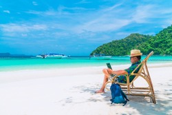 Asian business man in summer vacation trip, Traveler man relaxing on natural white sand beach using laptop, Andaman sea, Myanmar, Thailand, Destination place Asia, Holiday outdoor and travel concept